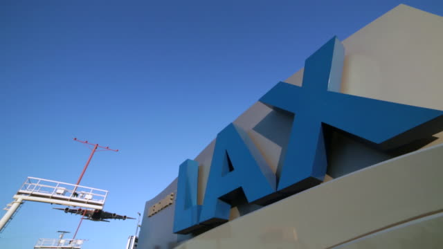 Jet Landing over LAX welcome sign