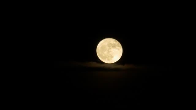 Jet plane passing full moon