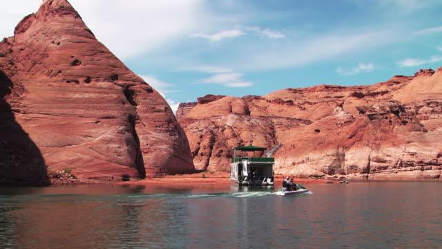stockvideo's en b-roll-footage met a jet ski passes a houseboat on lake powell. - powellmeer