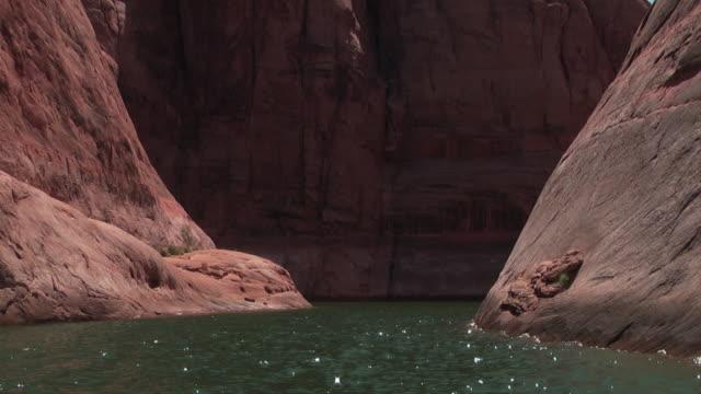 vídeos de stock e filmes b-roll de a jet skicreates a wake as it speeds through a canyon. - lago powell