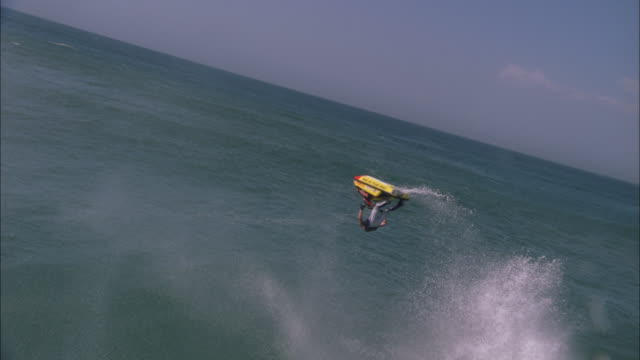 jet skier jumps off wave and launches into somersault, durban available in hd. - acquascooter video stock e b–roll