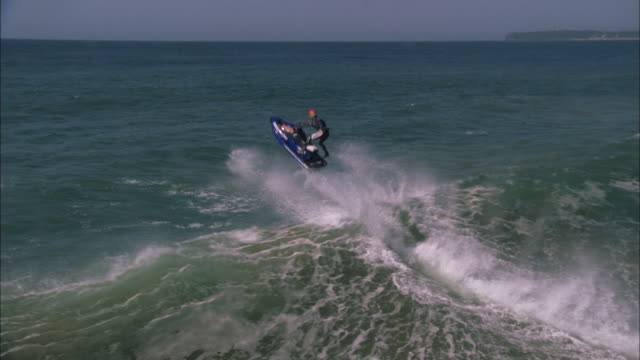 jet skier jumps off wave and lifts legs into air before landing on water, durban available in hd. - acquascooter video stock e b–roll