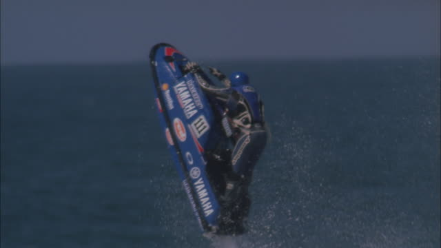 Jet skier performs jump and lifts hands off handlebars in mid-air, Durban Available in HD.