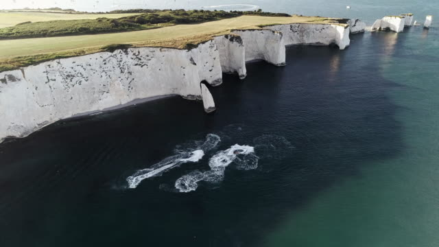 jet skis at the bottom of chalk cliffs filmed by drone, england, united kingdom - rock face stock videos & royalty-free footage