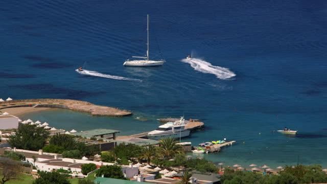 jet ski's & yacht in mirabello bay - acquascooter video stock e b–roll