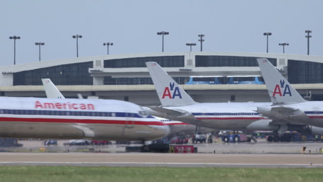 aa jetliner (md-80) crosses through frame with multiple planes parked at terminal in background/dfw international airport, dallas-fort worth, texas, usa - luftfahrtindustrie stock-videos und b-roll-filmmaterial