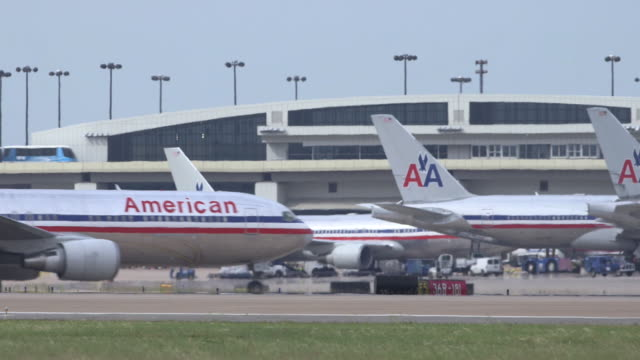 aa jetliner crosses through frame with multiple planes parked at terminal in background/dfw international airport, dallas-fort worth, texas, usa - asfalto video stock e b–roll