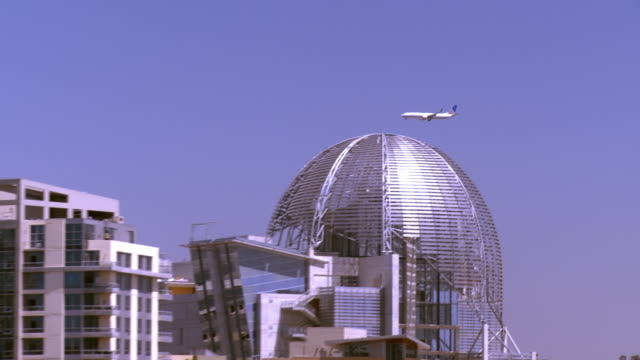 LS PAN jetliner on approach to airport flying over Petco Park and Gaslamp Quarter/ San Diego, California, USA