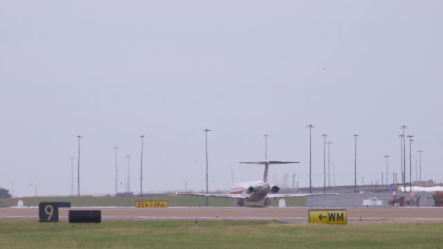 aa jetliner (mcdonnell douglas md-80) passes through frame on takeoff - extreme telephoto/dfw international airport, dallas-fort worth, texas, usa - dallas fort worth airport stock videos & royalty-free footage