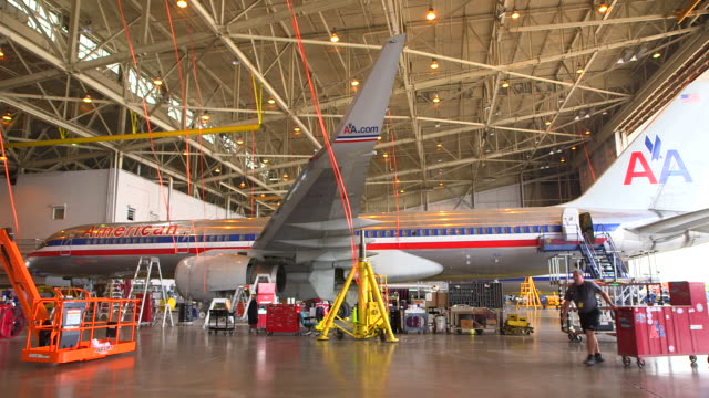 ws aa jetliner (boeing 757) serviced in hanger with worker pulling tool cart passing foreground/dfw international airport, dallas-fort worth, texas, usa - 飛行機格納庫点の映像素材/bロール