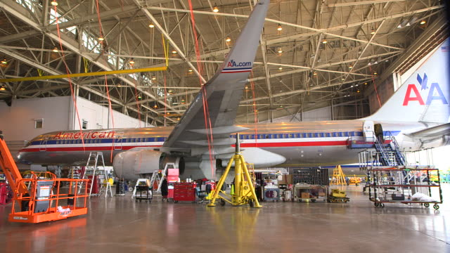 ws aa jetliner (boeing 757) serviced in hanger with workers in cart passing foreground/dfw international airport, dallas-fort worth, texas, usa - 飛行機格納庫点の映像素材/bロール