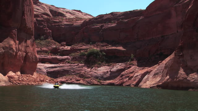 a jetski creates a wake as it speeds over lake powell. - lake powell stock videos and b-roll footage