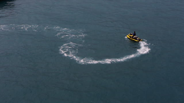 jetski doing circles, boat arrives in hong kong harbor - spoonfilm stock-videos und b-roll-filmmaterial