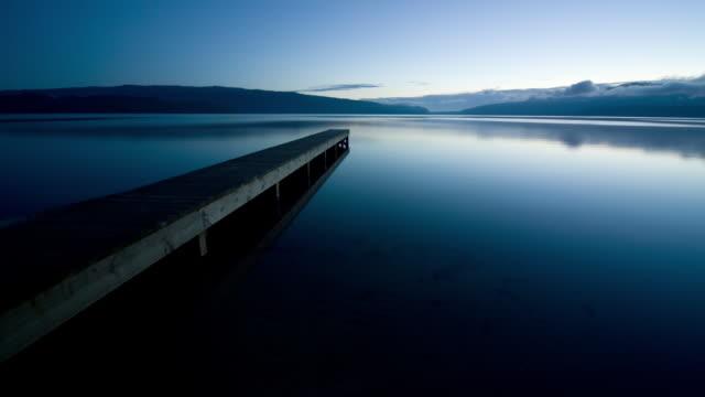 t/l, ws, jetty at lake tarawera, mount tarawera in background, dawn, rotorua, new zealand - rotorua stock videos and b-roll footage