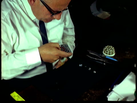 MONTAGE Jeweler grading a diamond with a stone gauge and then marking it while using a loupe for closer inspection / United States