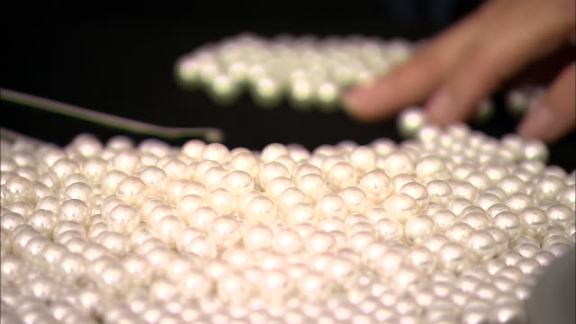 A jeweler uses tweezers to isolate, size and organize pearls.