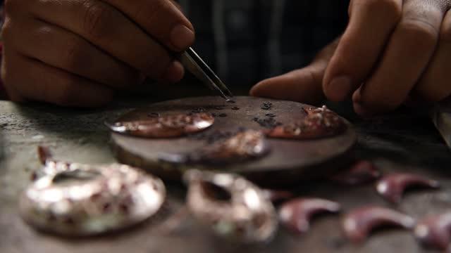 stockvideo's en b-roll-footage met jewelers making assamese jewelry in a traditional method in a assamese jewellery manufacturing unit in guwahati on 11 february 2019. assam jewellery... - zilver