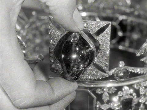 A jeweller holds the Black Prince Ruby next to the St Edwards Crown 1953