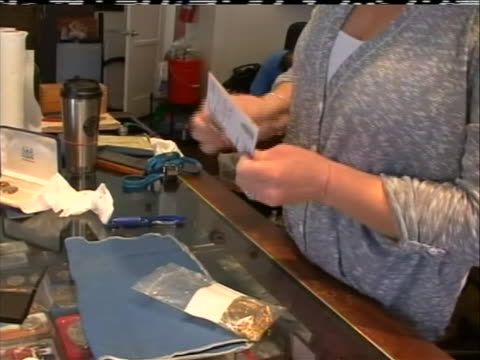 of jewelry store appraiser placing old unused pieces of gold jewelry that are being sold by the owner into a small plastic bag along with the receipt... - receipt stock videos & royalty-free footage