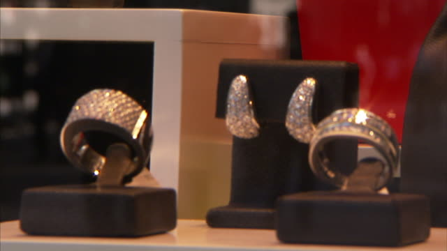A jewelry store displays diamond earrings and bracelets in a window as shoppers walk by.