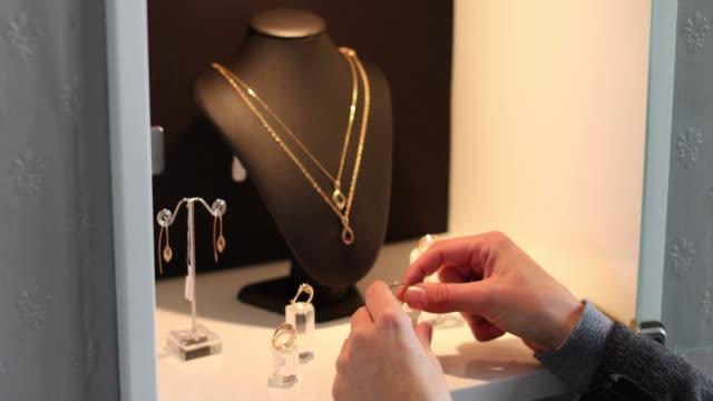 vídeos y material grabado en eventos de stock de el dueño de una joyería organizando su vitrina. - una mujer de mediana edad solamente