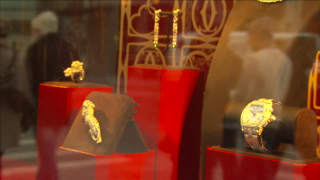 a jewelry store window reflects passing pedestrians and traffic in new york city. - schmuck stock-videos und b-roll-filmmaterial