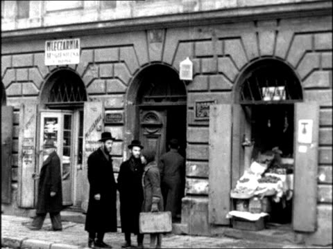 jewish ghetto in prewar poland children around man with balloons on cobblestone street / man blowing balloon / men and woman talking in front of... - anno 1938 video stock e b–roll