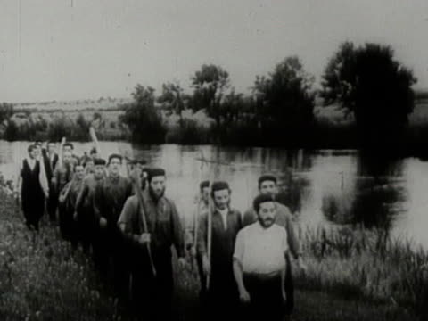 Jewish immigrants in Palestine walk along riverbank with farming tools
