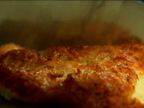 vídeos y material grabado en eventos de stock de jewish latkas potato pancake is cut with knife in bakery jewish hanukkah festival golders green london - golders green