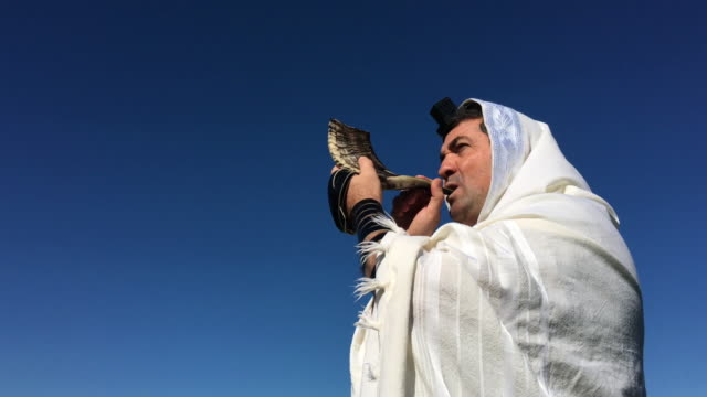 Jewish man blows a Shofar on the Jewish High Holidays