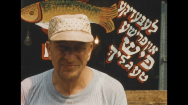 of jewish man in new york's lower east side standing in front of a fish market storefront window with a drawing of a fish and hebrew characters. on... - judaism stock videos & royalty-free footage