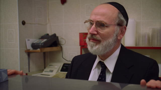 A Jewish man stands behind a restaurant counter. Available in HD.