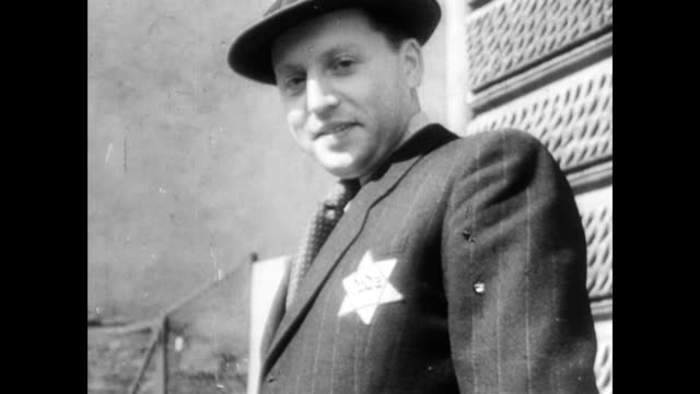 jewish men with stars of david on their clothes walking down the streets of dombrova / jewish men and women in a crowd smiling for the camera. jewish... - 1939 stock videos & royalty-free footage