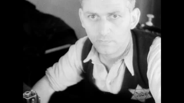 vidéos et rushes de jewish men working in a textile factory sitting behind sewing machines / male supervisor checks work / men sewing. polish jewish men working in... - judaism