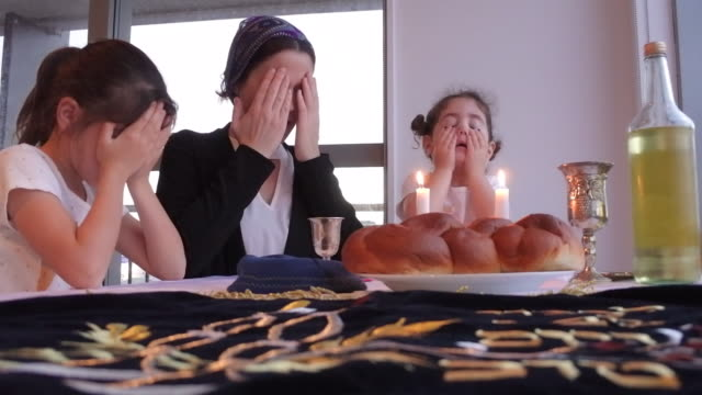 jewish mother and daughters light sabbath candles - coda di cavallo video stock e b–roll