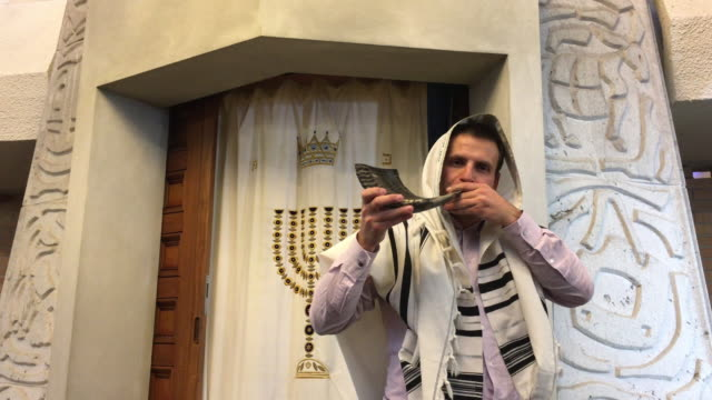 Jewish Rabbi blows Shofar in a synagogue