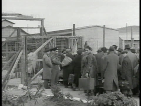 vídeos de stock, filmes e b-roll de palestine jewish refugees displaced persons walking in line into refugee camp ms women children walking through gate ms soldier official directing... - 1945
