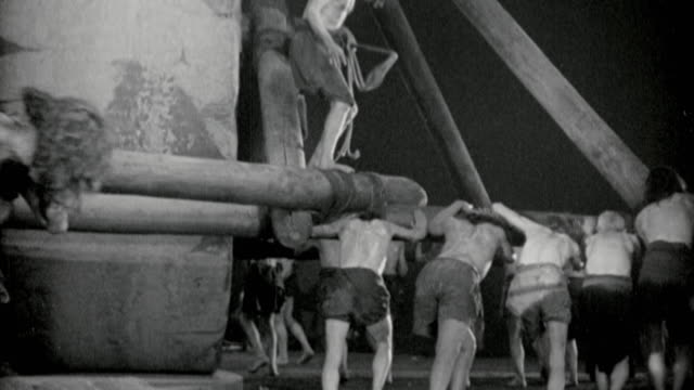b/w jewish slaves pushing spokes to turn giant wheel while being whipped / ben-hur (1925) - authority stock videos & royalty-free footage