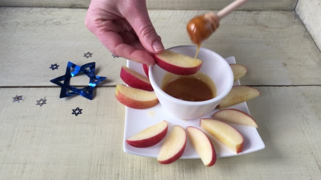 Jewish Woman Serving a Honey Bowl with a Honey Dipper and Fresh Apple Cuts on Rosh Hashanah The Jewish New Year Holiday