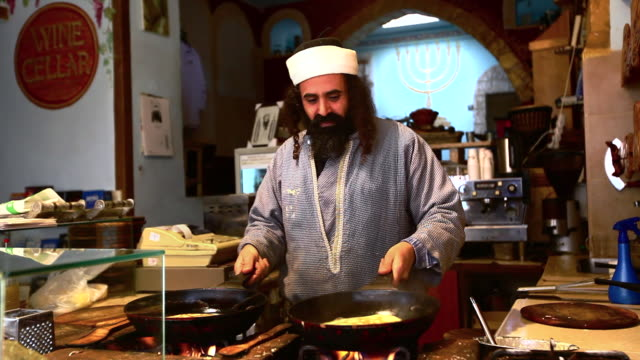 a jewish yemenite man flips murtabak crepes in two skillets at the same time. - throwing stock videos & royalty-free footage