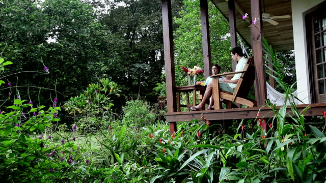 jib crane shot of man and woman sitting on porch of cabana in lush jungle forest. - adirondack chair stock videos & royalty-free footage