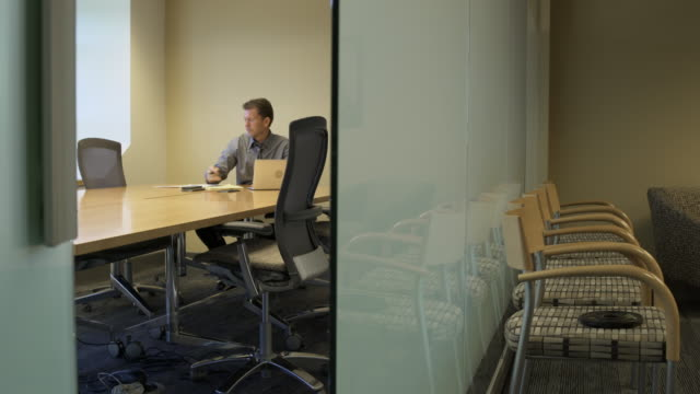 jib shot of a businessman working in a conference room - jib shot stock videos & royalty-free footage