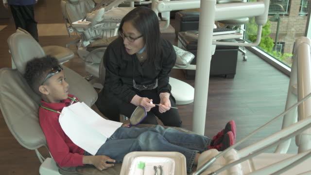 vídeos y material grabado en eventos de stock de jib shot of a dentist examining a boy - jib shot