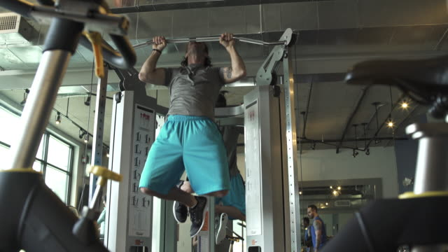 jib shot of a man doing pull-ups in a gym - ランニングショートパンツ点の映像素材/bロール
