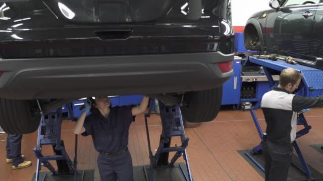 Jib shot of a mechanic examining a car
