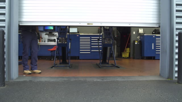 jib shot of a mechanic opening a garage door - repair garage stock videos & royalty-free footage