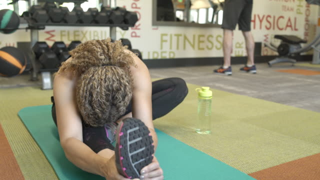jib shot of a woman stretching in a gym - curly stock videos & royalty-free footage