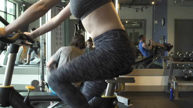 Jib shot of a woman using a stationary bike