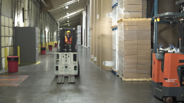 jib shot of a worker driving a forklift - jib shot stock videos & royalty-free footage