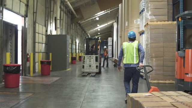 jib shot of people working in a warehouse - hubwagen stock-videos und b-roll-filmmaterial